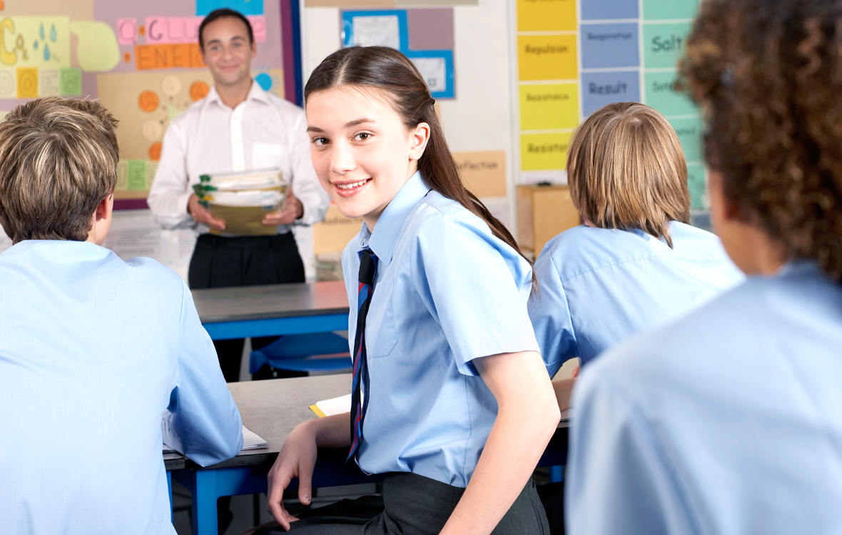 Girl with school uniform sitting in classroom